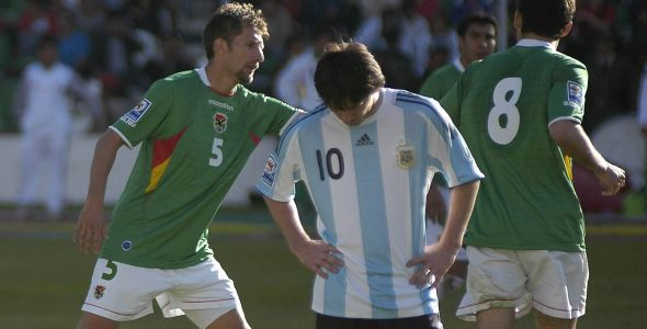 Argentina's Lionel  Messi reacts as Bolivia's Ronald Rivero and Ronald Garcia celebrate a goal during their 2010 World Cup qualifying soccer match in La Paz