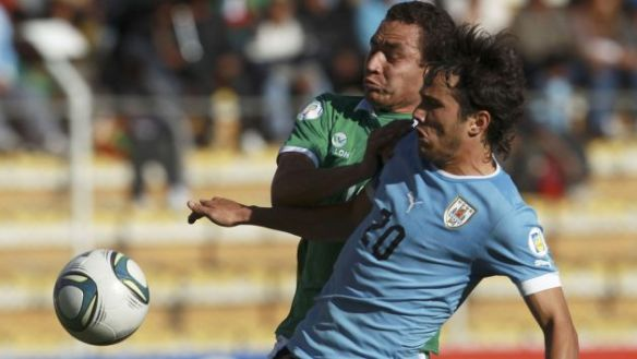 Uruguay's Alvaro Gonzalez, right, battles for the ball with Bolivia's Gualberto Mujica during a 2014 World Cup qualifying soccer match in La Paz, Bolivia, Tuesday, Oct. 15, 2012. (AP Photo/Juan Karita)